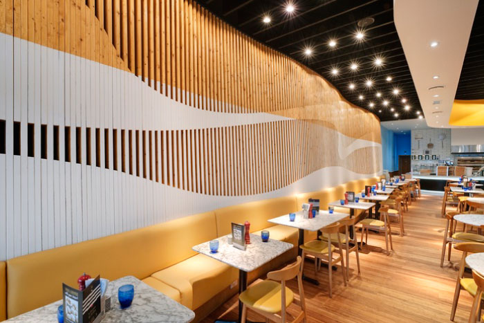 The repeating wood slats on the wall of this pizza shop by Baynes & Co  Designers creates a playful rhythm and draws your eye through the space.