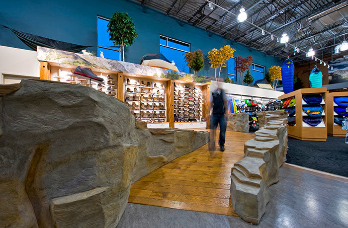 Custom Raised Footwear Section Defined by an Organic Faux Rock Wall for the Grouse River Kelowna Retail Design by Hatch Interior Design